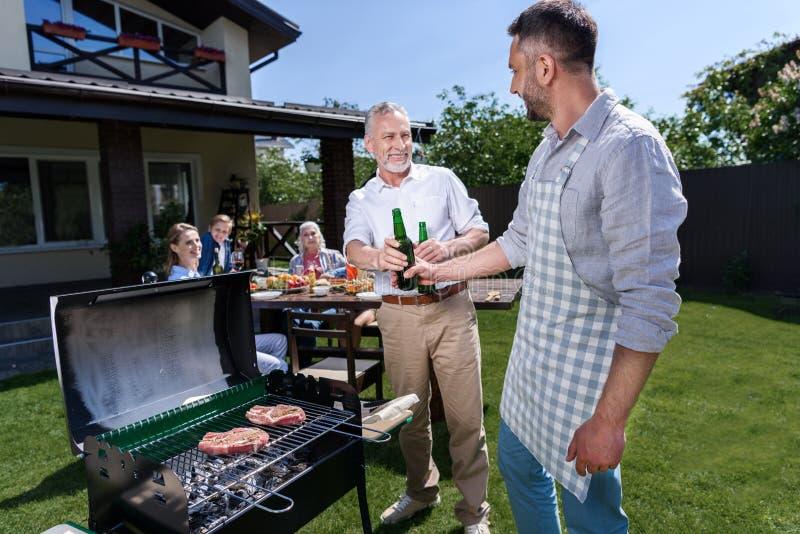 资深父亲和成人儿子饮用的啤酒,当烤肉户外时 库存图片
