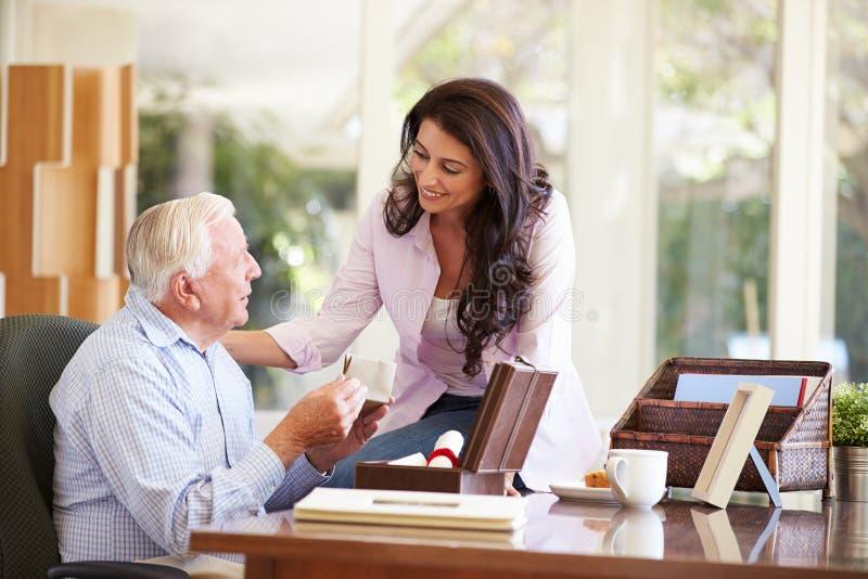 资深父亲谈论文件与成人女儿 免版税库存图片