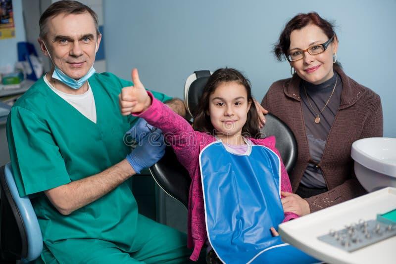 资深牙医和女孩画象有她的母亲的牙齿参观的在牙齿办公室 免版税库存照片