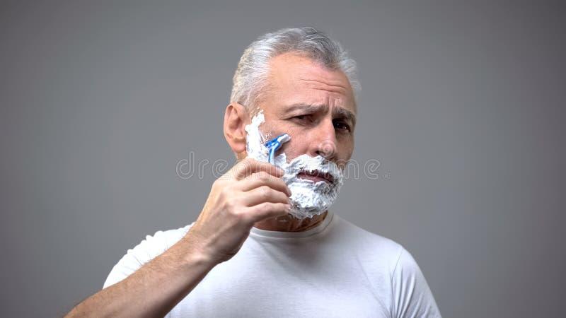 资深男性刮,变老的skincare奶油,早晨定期仪式,传统 库存照片