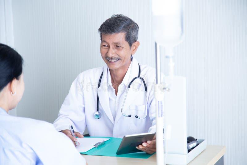资深男性医生微笑谈论与讲话与他的资深患者 免版税库存图片