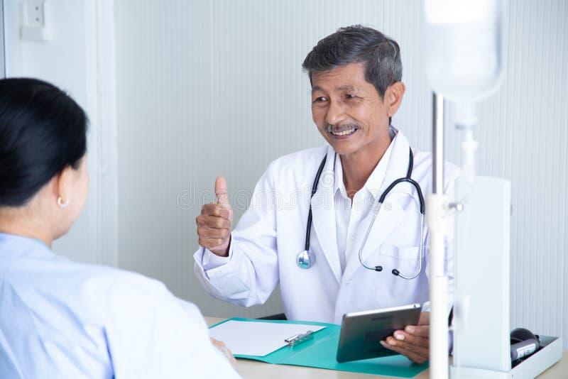 资深男性医生微笑谈论与讲话与他的资深患者 免版税库存照片