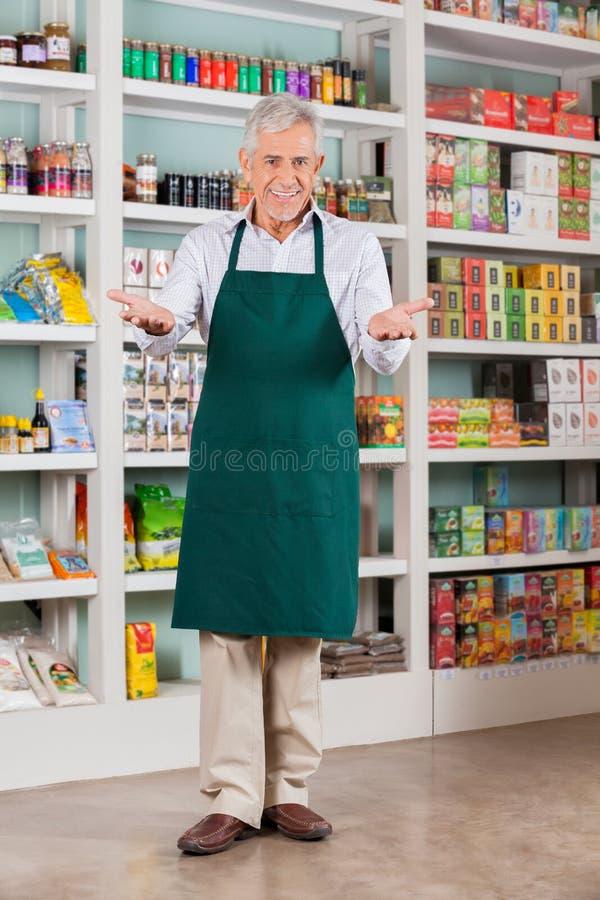资深男性店主欢迎在超级市场 库存图片