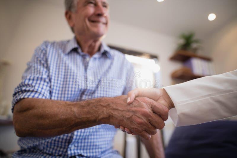 资深男性患者与女性治疗师握手 免版税库存照片