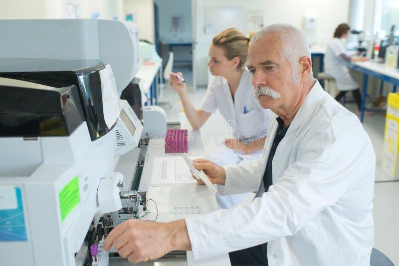 资深男性研究员执行的科学研究对实验室 免版税库存照片