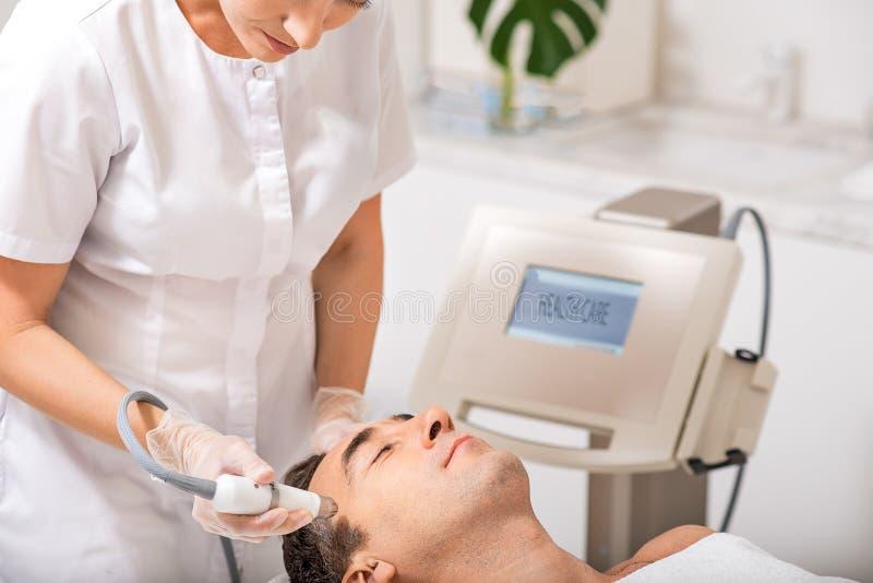 资深男性耐心享用的超声波脸面护理按摩 库存图片