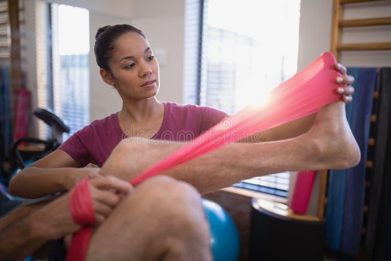 资深男性耐心拉扯的抵抗带的低部分由女性治疗师的 库存照片