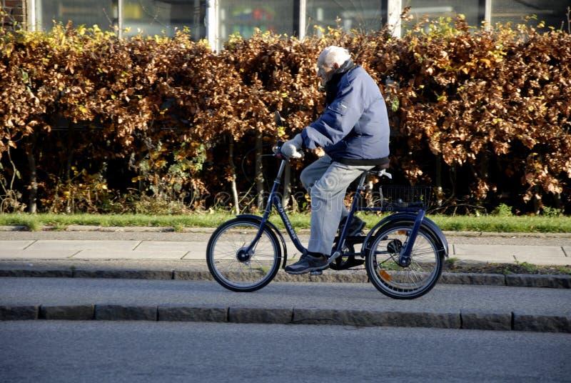 资深男性骑三个轮子自行车 免版税库存照片