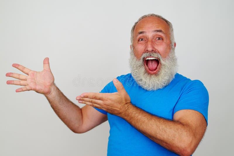 资深白胡子的人高兴和指向某事机智 免版税库存图片