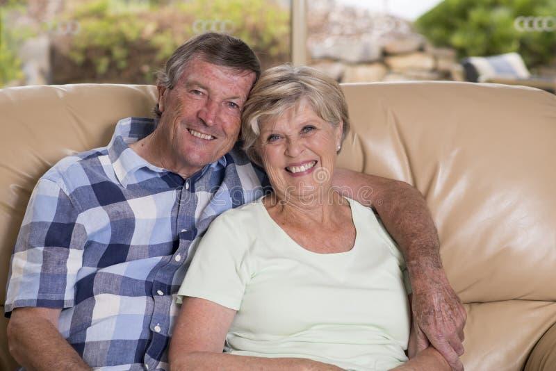 资深美好的中年夫妇大约70岁看起来微笑的愉快的一起在家客厅沙发的长沙发甜在生活中 库存图片