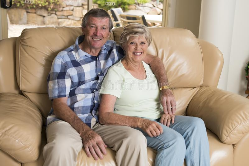 资深美好的中年夫妇大约70岁看起来微笑的愉快的一起在家客厅沙发的长沙发甜在生活中 图库摄影