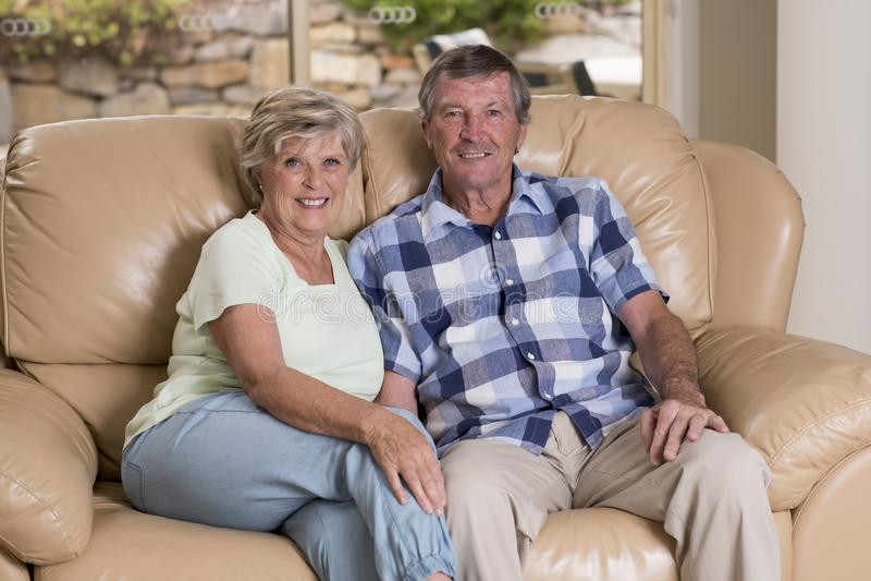 资深美好的中年夫妇大约70岁看起来微笑的愉快的一起在家客厅沙发的长沙发甜在生活中 库存照片