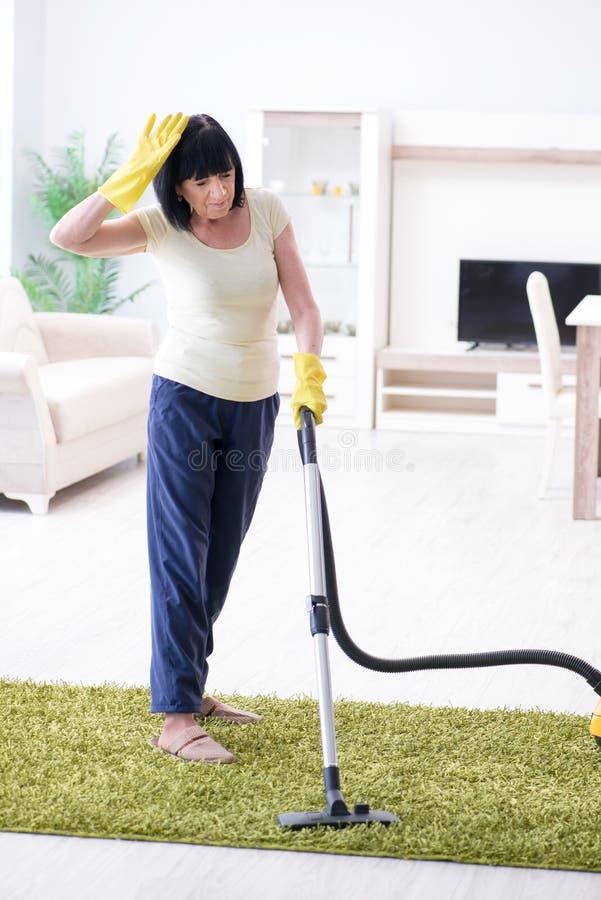 资深老妇人在真空清洁房子以后疲倦了 免版税库存照片
