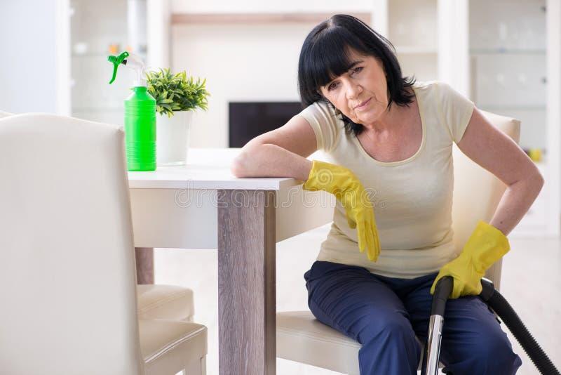 资深老妇人在真空清洁房子以后疲倦了 免版税库存图片