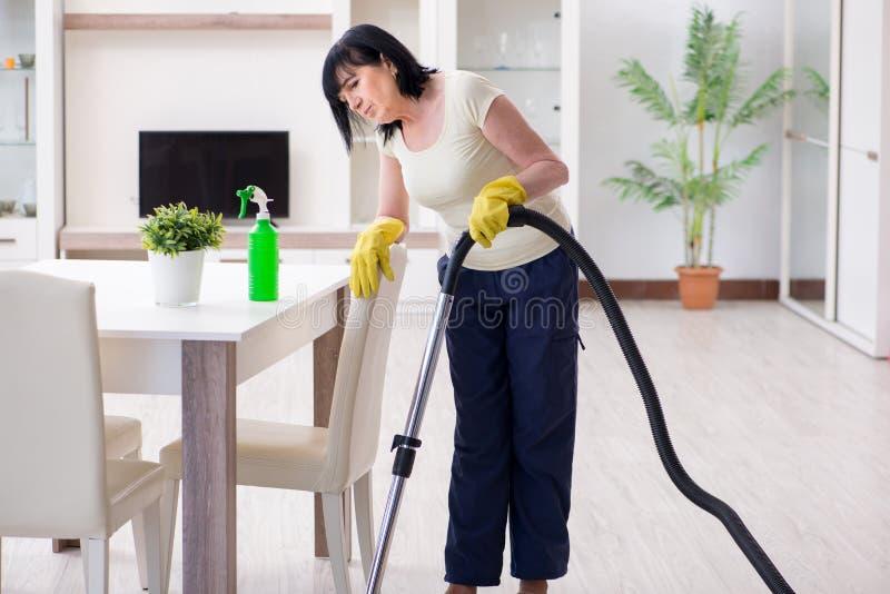 资深老妇人在真空清洁房子以后疲倦了 库存照片