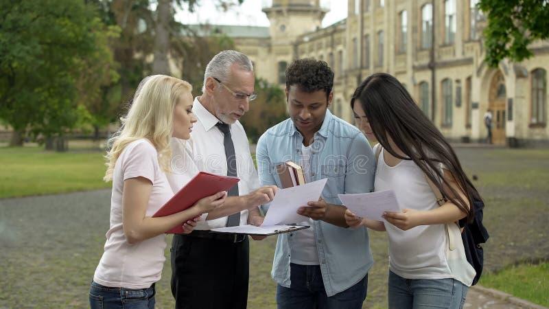 资深老师谈论考试成绩与小组学生,合作 免版税库存图片