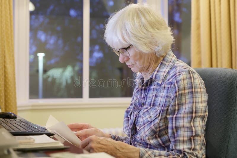 资深老年长人学会计算机的和网上退休金和银行业务互联网技能防止受到欺骗 免版税库存照片