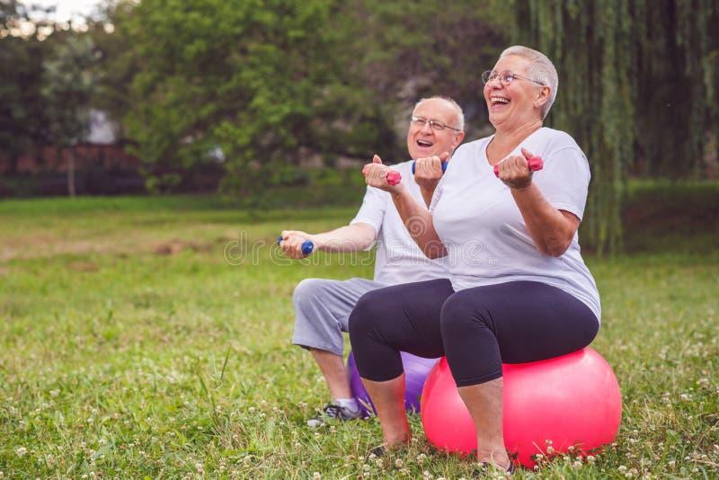 资深资深体育的妇女和人心脏锻炼坐与哑铃的健身球 免版税库存照片