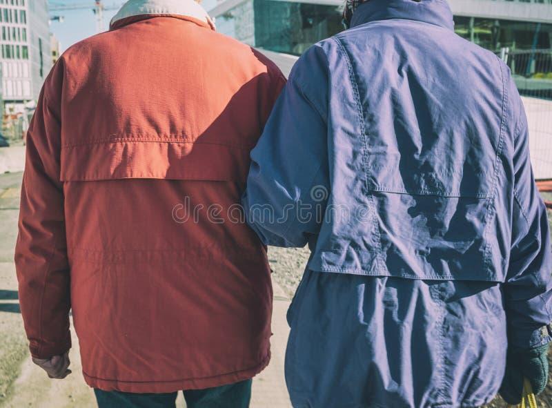 资深走在城市的夫妇后方拥抱的胳膊在冬天 图库摄影