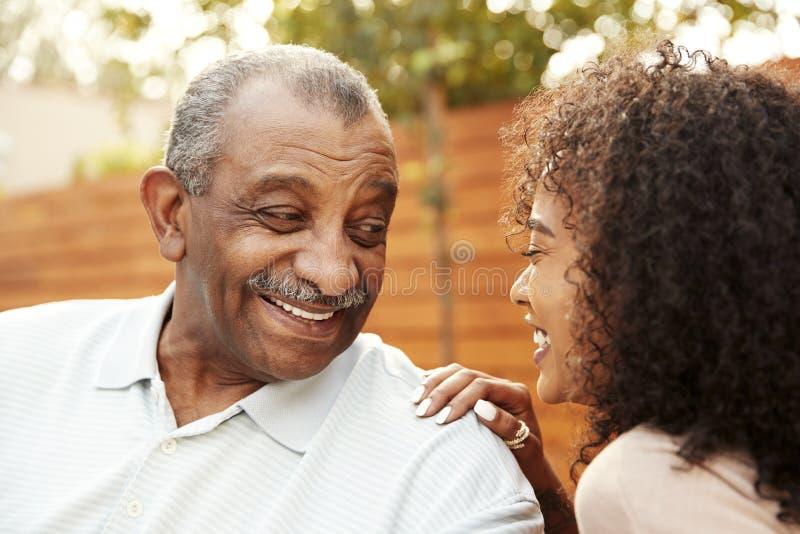 资深非裔美国人的笑人和他的成人的孙女户外,关闭  库存照片