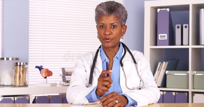 资深非洲医生坐在书桌和谈话与照相机 库存照片