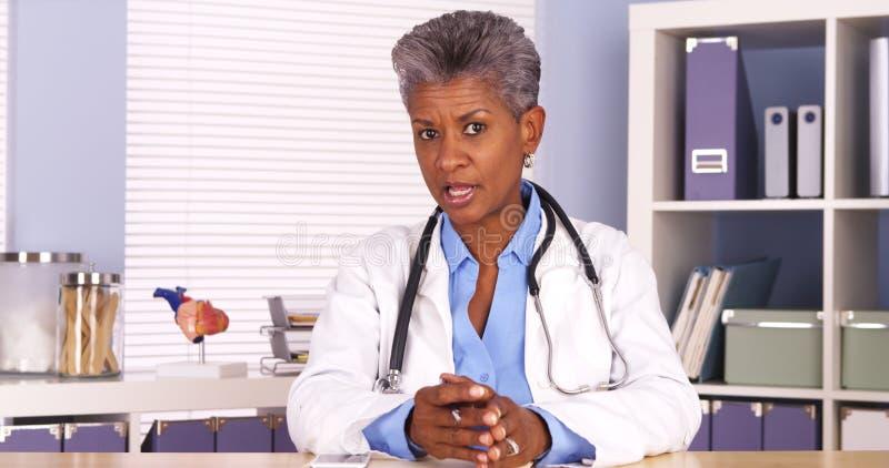 资深非洲医生坐在书桌和谈话与照相机 免版税库存照片