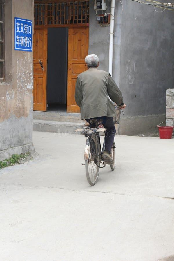 资深骑自行车者在大圩,中国古老村庄  库存照片