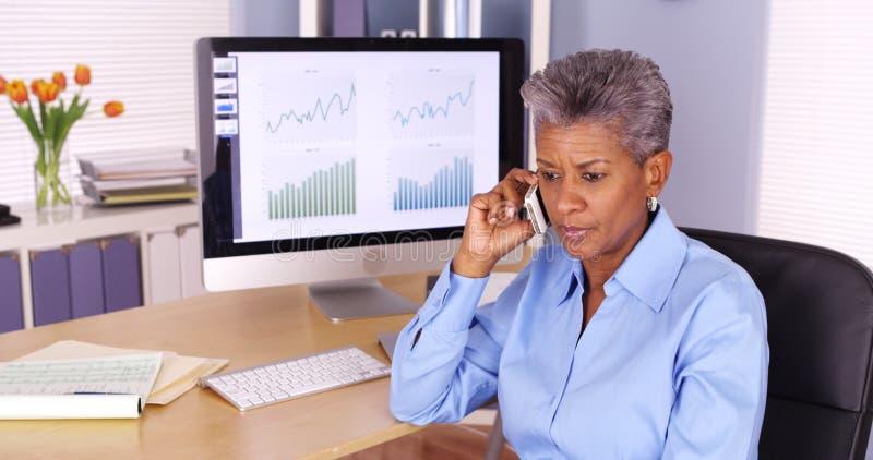 资深黑人女商人谈话在电话用计算机 免版税库存图片