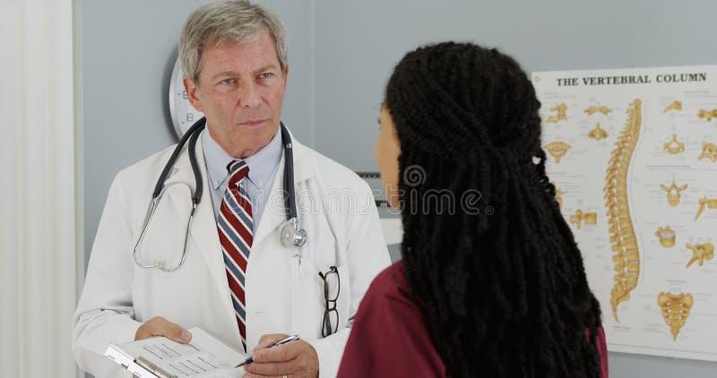 资深医生和年轻人护理谈论患者的结果 库存照片
