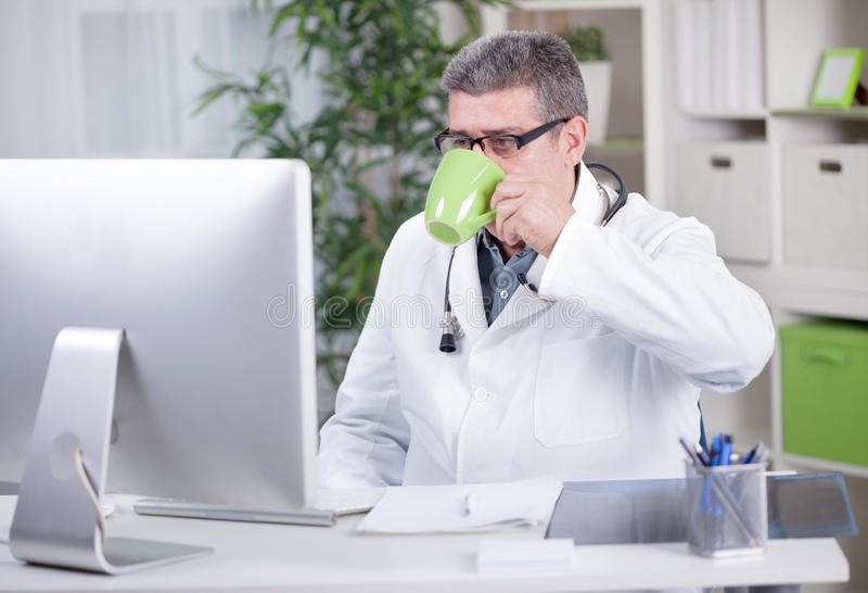 资深医生在研究计算机饮料cof的办公室 库存图片