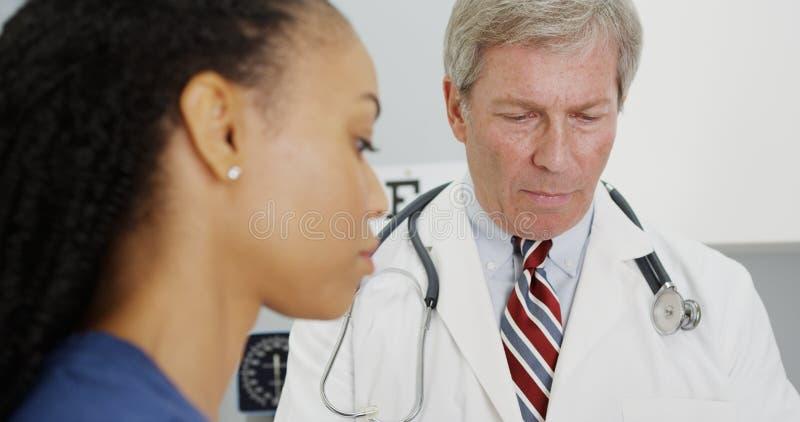 资深医生谈话与妇女在办公室 图库摄影