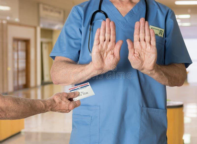 资深医生洗刷拒绝医疗保障卡片 免版税库存照片