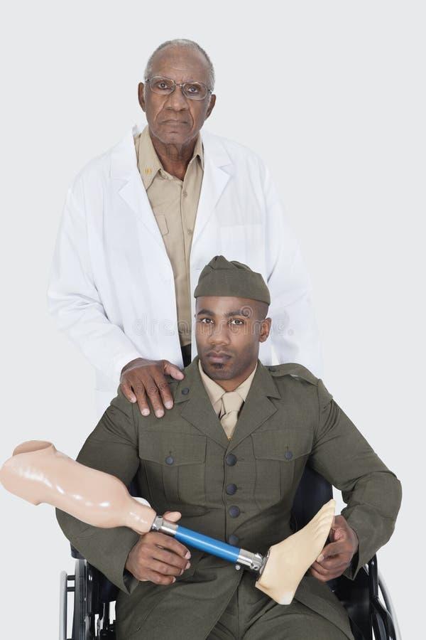 资深医生画象有拿着人为肢体的美军官员的,他在灰色背景的轮椅坐 库存照片