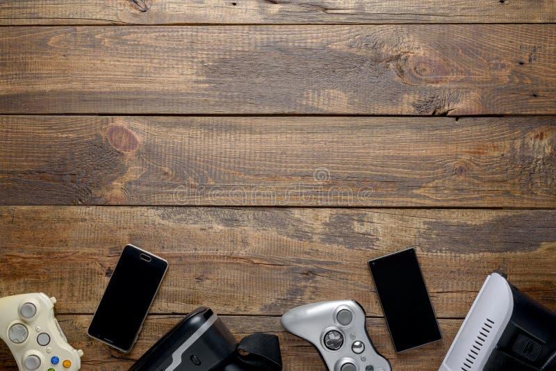 赌博、gamepads、智能手机和VR玻璃的设计版面在与拷贝空间的织地不很细木背景 库存照片