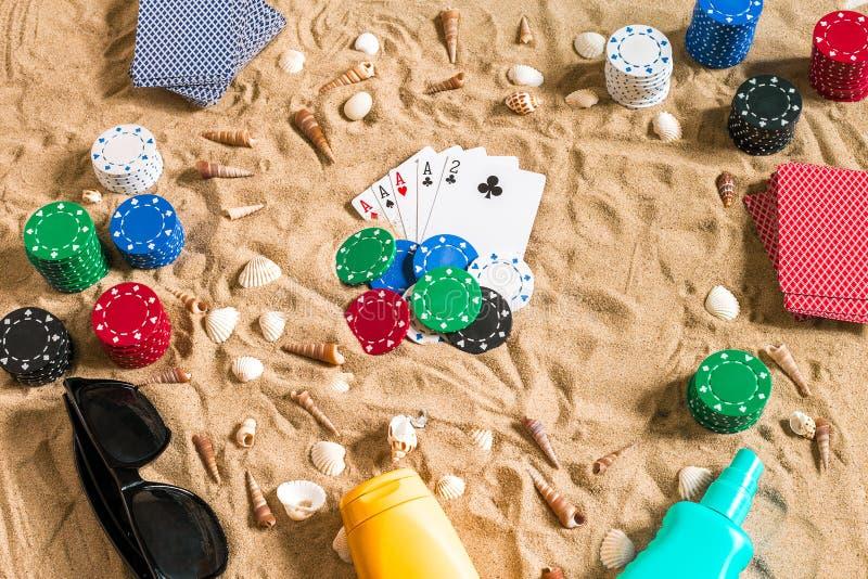 赌博在假期概念-与贝壳、色的纸牌筹码和卡片的白色沙子 顶视图 免版税库存图片