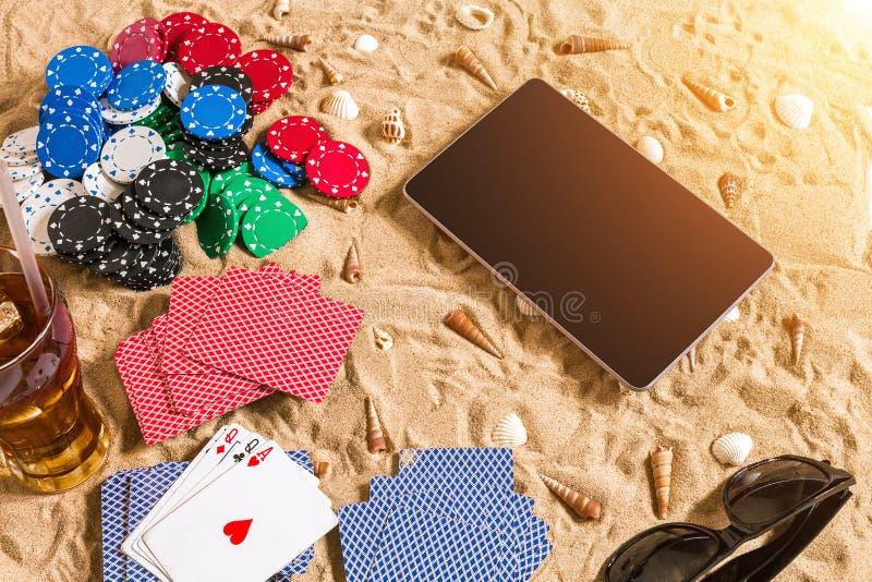 赌博在假期概念-与贝壳、色的纸牌筹码和卡片的白色沙子 顶视图 库存照片