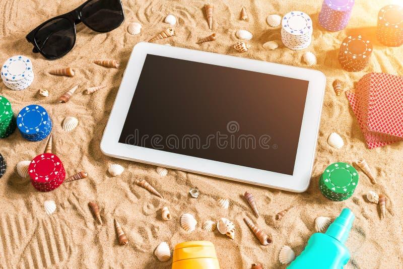 赌博在假期概念-与贝壳、色的纸牌筹码和卡片的白色沙子 顶视图 图库摄影