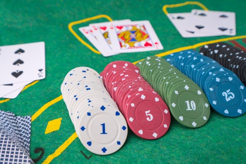 赌博娱乐场或堆的芯片赌博的象征 金钱或现金容量堆比赛的象啤牌、卡片和大酒杯,轮盘赌 免版税库存图片