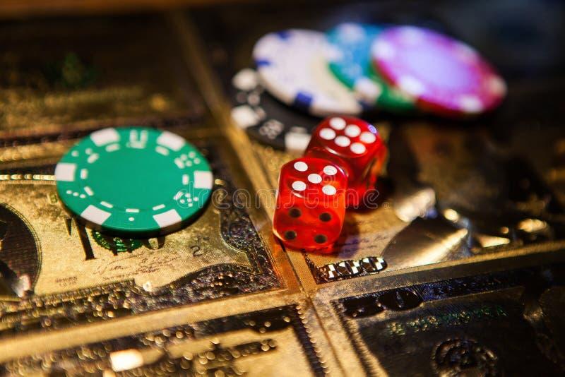 赌博娱乐场红色切成小方块和赌博娱乐场在金黄美元票据的纸牌筹码 免版税库存图片