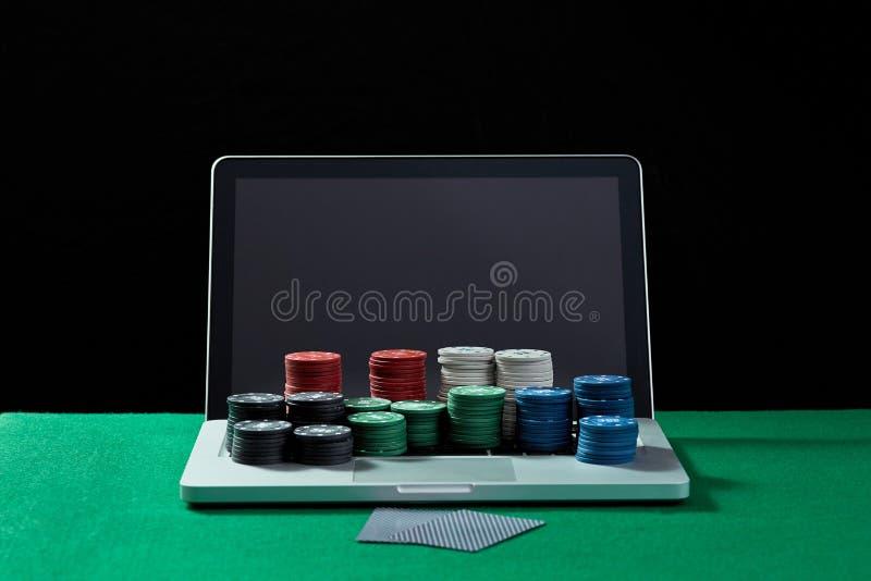 赌博娱乐场芯片和卡片在键盘笔记本在选材台上 免版税库存照片