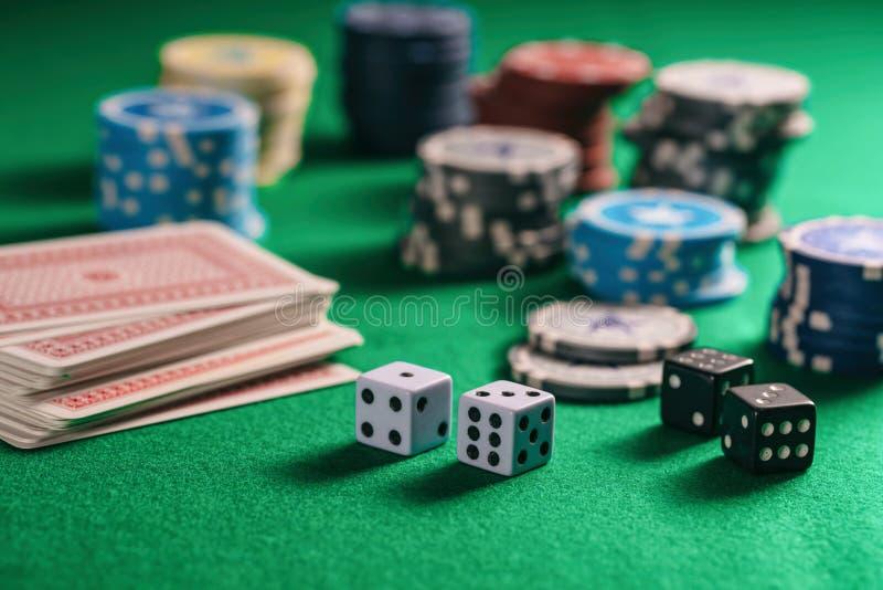 赌博娱乐场,赌博 纸牌筹码堆、纸牌和模子在绿色感觉的背景 免版税库存图片