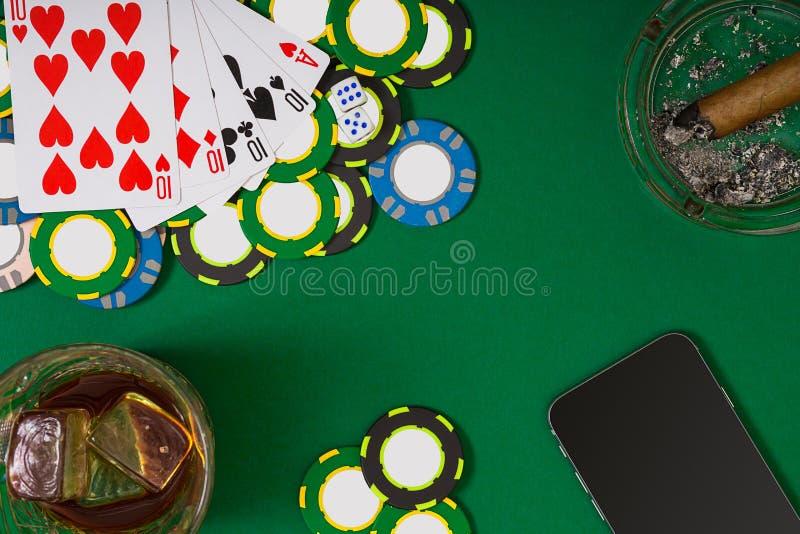 赌博,时运和娱乐概念-接近赌博娱乐场芯片,威士忌酒玻璃、纸牌和雪茄在绿色 免版税库存图片