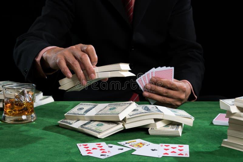 赌客放赌注入堆钞票 免版税库存照片