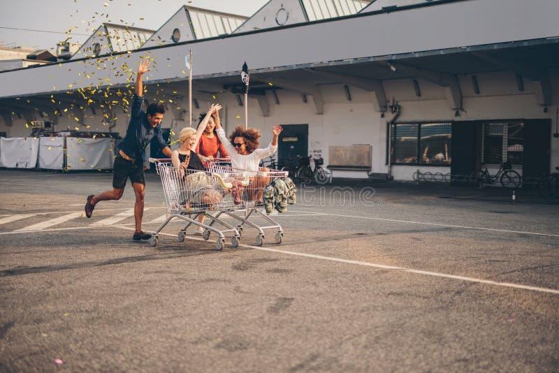 赛跑与在路的购物车的朋友 免版税库存照片