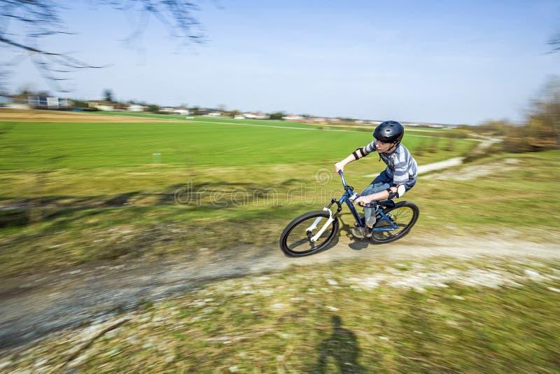 赛跑与他的土自行车的十几岁的男孩 库存图片