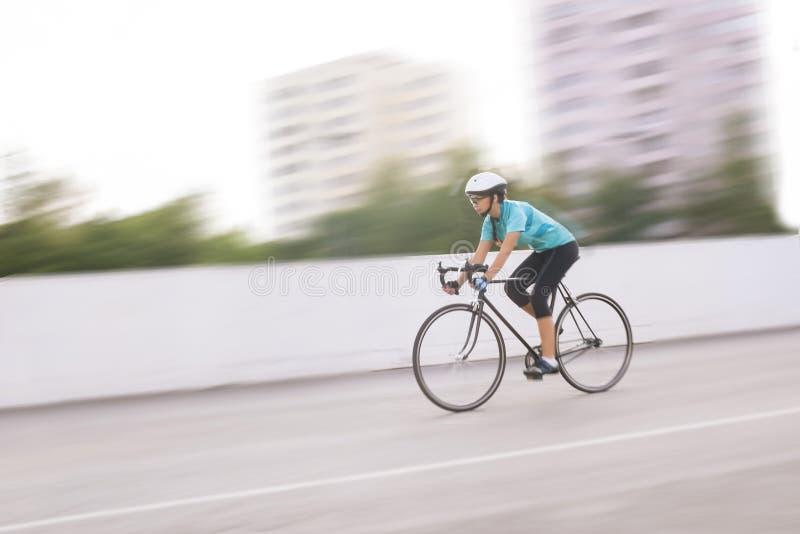 赛跑在自行车的年轻女运动员。行动被弄脏的图象 图库摄影