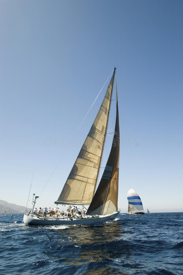 赛跑在蓝色海洋的风船与天空 免版税库存图片