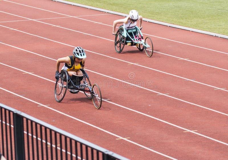 赛跑在轨道的轮椅的两个高中女孩 库存图片