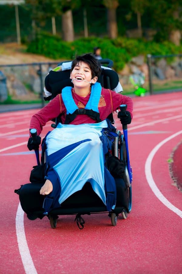 赛跑在轨道路线的轮椅的年轻残疾男孩 库存图片