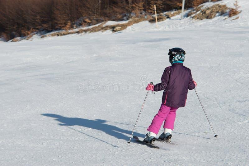 赛跑在雪的小滑雪者 库存照片
